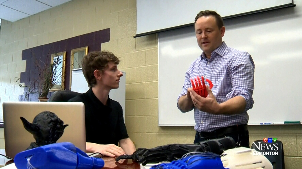 Lucas Whitfield (left) and teacher Aaron Dublenko are working with a 3D printer to make prosthetic hands for children who need them.