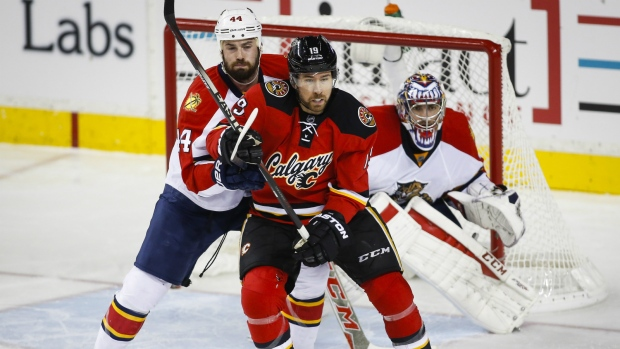 Florida Panthers' Erik Gudbranson, left, and Calgary Flames' David Jones, centre, tangle as Panthers goalie Al Montoya, right, looks on during second period NHL hockey action in Calgary, Wednesday, Jan. 13, 2016. (Jeff McIntosh / THE CANADIAN PRESS)