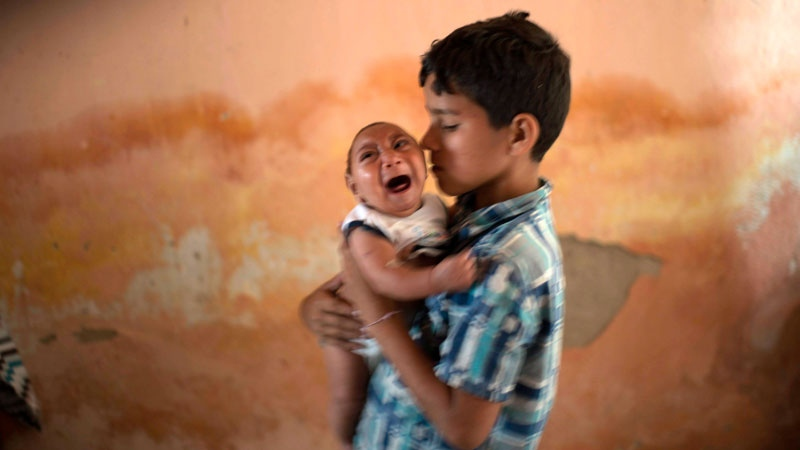 Ten-year-old Elison holdshis 2-month-old brother Jose Wesley at their house in Poco Fundo, Pernambuco state, Brazil on In this Dec. 23, 2015. (AP /Felipe Dana)