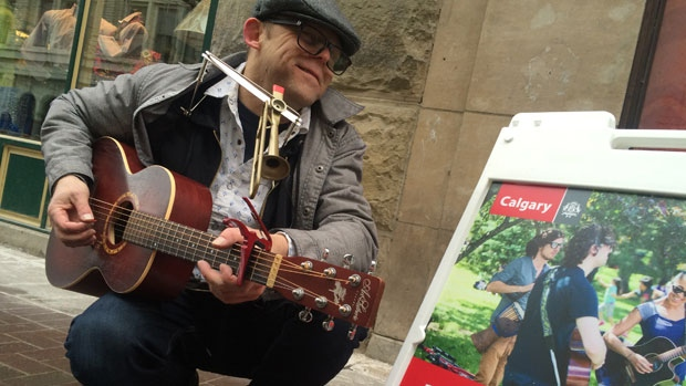 John Rutherford, a street performer plays his guitar at one of Calgary's new designated busk stops.