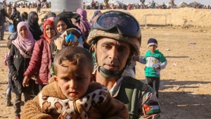 A Jordanian soldier carries a Syrian refugee child at the Hadalat border crossing, located near the northeastern Jordanian border with Syria and Iraq on Jan. 14, 2016.  (AP / Raad Adayleh)