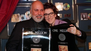 "Singer Celine Dion cuddles up to her manager and fiancé Rene Angelil after being presented with a diamond record for her album ""The Colour of My Love"" Thursday in Montreal, Nov. 24, 1994. (The Canadian Press / Paul Chiasson)"