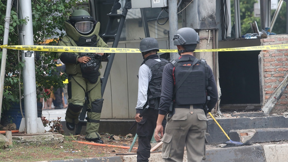 Members of the police bomb squad inspect a police post where an explosion went off in Jakarta, Indonesia, Thursday, Jan. 14, 2016. (AP / Tatan Syuflana)