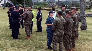 Military officials and Honolulu Police Department officers talk at a beach park where search and rescue officials are meeting in Haleiwa, Hawaii, Friday, Jan. 15, 2016.