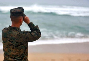This Friday, Jan. 15, 2016 photo provided by the U.S. Marine Corps shows a Marine Officer attached to Marine Heavy Helicopter Squadron 463 uses binoculars to search for debris of a helicopter mishap in Haliewa Beach Park, Hawaii. (Cpl. Ricky S. Gomez/U.S. Marine Corps via AP)