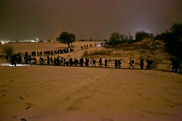 Migrants walk through snow