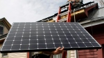 In this April 29, 2013, file photo, Jon Kirkpatrick carries a solar panel up to Bevan Walker for an installation for SunCommon in Montpelier, Vt. (AP Photo / Toby Talbot, File)