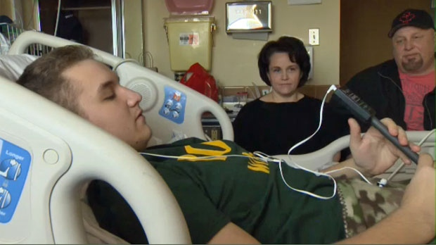 Alex plays his electronic bagpipe in his hospital bed while his parents look on