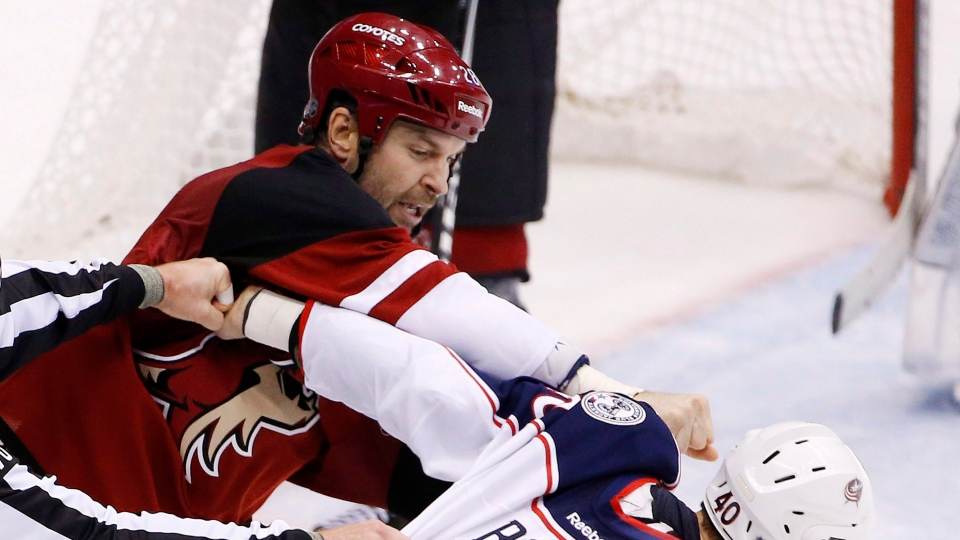In this Dec. 17, 2015 file photo, Arizona Coyotes' John Scott, left, punches Columbus Blue Jackets' Jared Boll (40) during a fight in the second period of an NHL hockey game. (AP / Ross D. Franklin)