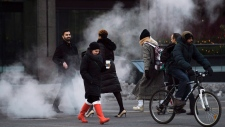 People walk through the steam on a cold day in downtown Toronto on Monday, January 4, 2016. (Nathan Denette / THE CANADIAN PRESS)