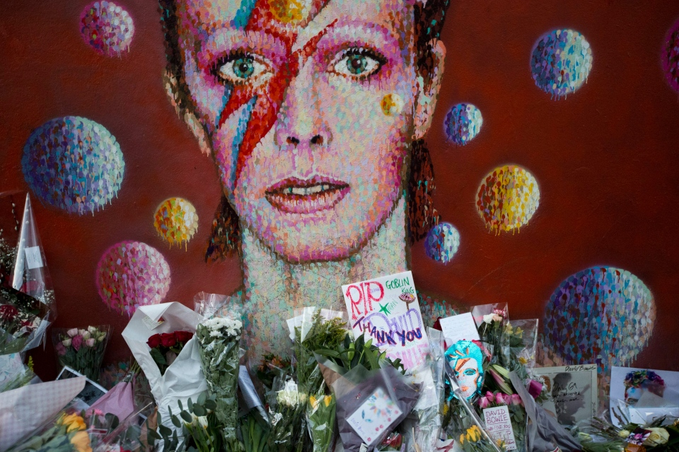 Tributes lie beneath a mural of British singer David Bowie by artist Jimmy C in Brixton, south London, Tuesday, Jan. 12, 2016. (Matt Dunham / AP Photo)