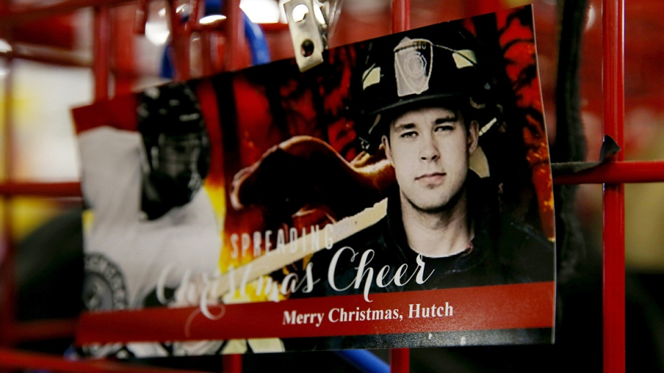 A photo of Matthew Hutchinson appears on a Christmas card he was given by members of the Geneseo Fire Department, where he served as a volunteer firefighter, in Geneseo, N.Y., Monday, Jan. 18, 2016. (Max Schulte / Democrat & Chronicle via AP)
