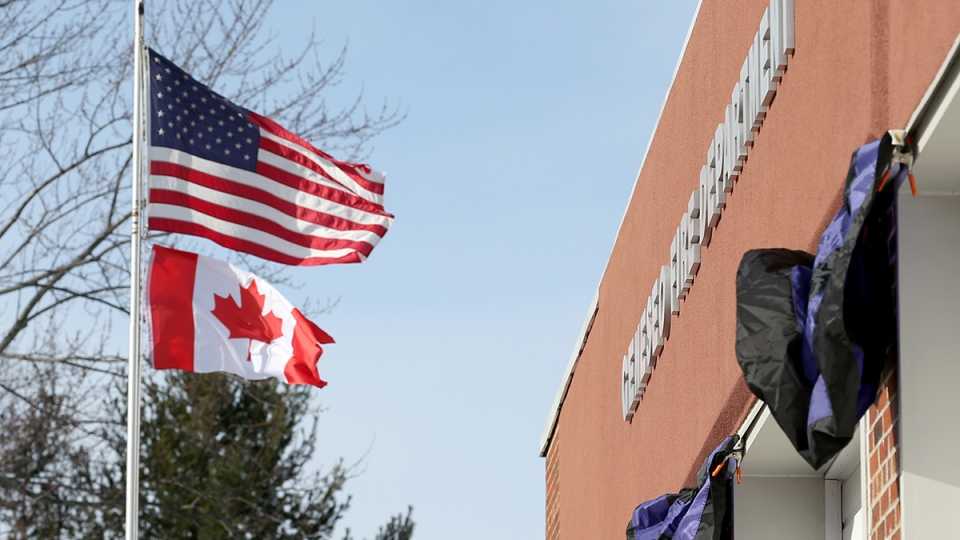 The Canadian flag, which was brought over to the Geneseo Fire Department by teammates of Matthew Hutchinson's hockey team, is raised at the fire department in Genesio, N.Y., Monday, Jan. 18, 2016. (Max Schulte / Democrat & Chronicle via AP)