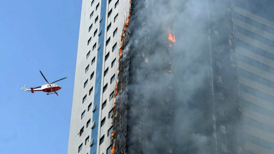A helicopter hovers over a skyscraper which caught fire in Sharjah, United Arab Emirates on Oct. 1, 2015. (AP)