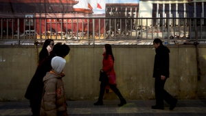 People walk past posters of Tiananmen Gate, left, and the Great Hall of the People on display near a building under construction in Beijing, Tuesday, Jan. 19, 2016. (AP Photo/Andy Wong)