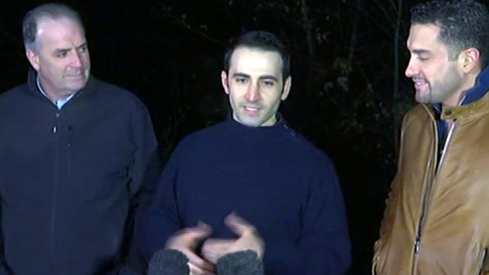 In this image made from video, former U.S Marine Amir Hekmati, centre, is flanked by Michigan congressman Dan Kildee, left, and Hekmati's brother-in-law Ramy Kurdi as he speaks to the media in Landstuhl, Germany, Tuesday, Jan. 19, 2016. (APTN via AP)