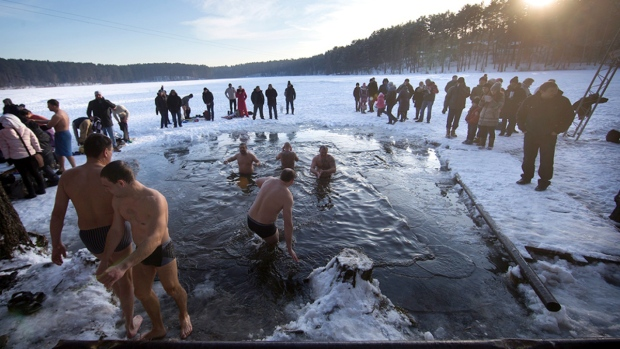 Lithuanian Orthodox believers bathe in the icy water on Epiphany in a lake outside Vilnius, Lithuania, Tuesday, Jan. 19, 2016. (AP / Mindaugas Kulbis)