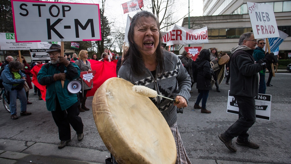 Patricia Kelly, of the Sto:lo First Nation, chants and beats a drum during a protest outside National Energy Board hearings on the proposed Trans Mountain pipeline expansion in Burnaby, B.C., on Tuesday, Jan. 19, 2016. (Darryl Dyck / THE CANADIAN PRESS)