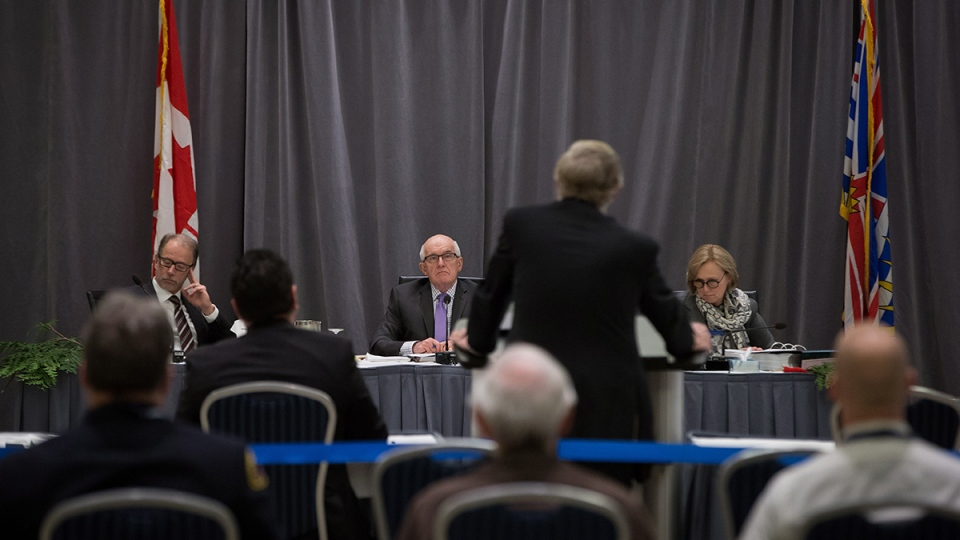 NEB panel members Philip Davies, back from left, David Hamilton and Alison Scott listen as James Reynolds, a lawyer representing the Musqueam First Nation, speaks during National Energy Board hearings on the proposed Trans Mountain pipeline expansion in Burnaby, B.C., on Tuesday, Jan. 19, 2016. (Darryl Dyck / THE CANADIAN PRESS)