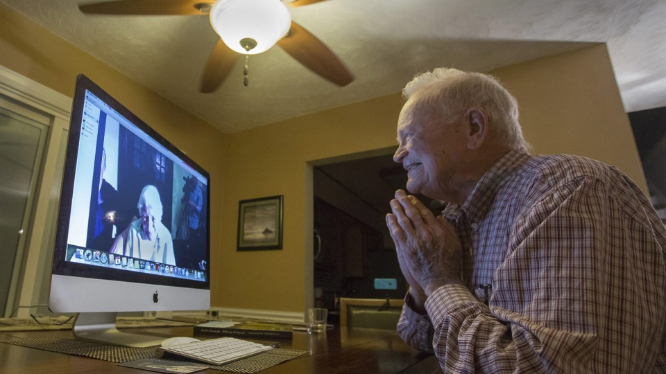 In this photo taken Nov. 6, 2015, Norwood Thomas, 93, talks with Joyce Morris via Skype from his home in Virginia Beach, Va. (Bill Tiernan/The Virginian-Pilot via AP)