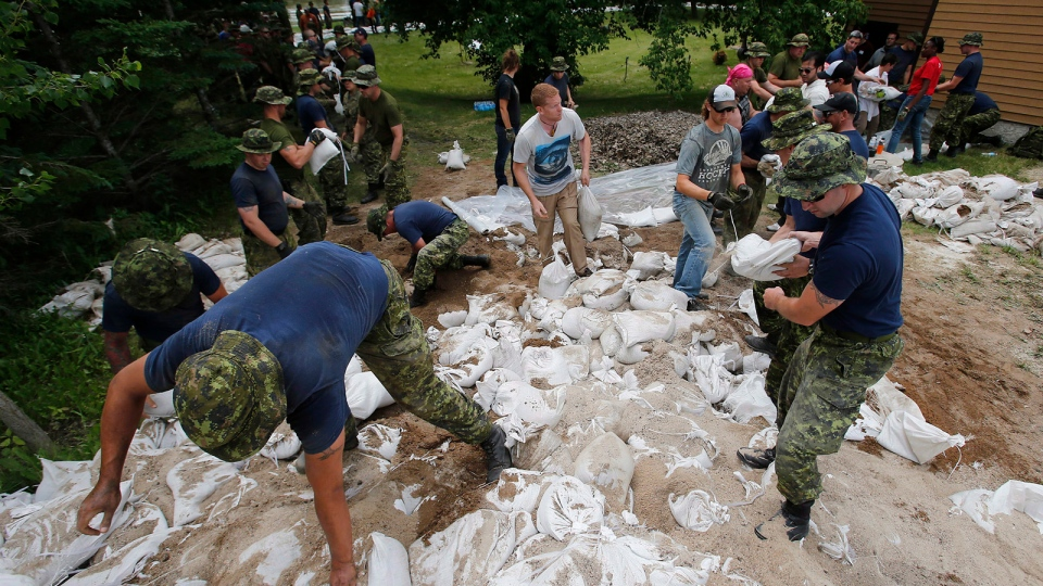 Soldiers from 17 Wing in Winnipeg sandbag in St. Francois Xavier, Man., Tuesday, July 8, 2014. (John Woods / THE CANADIAN PRESS)