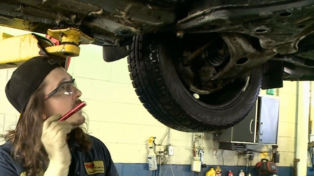 A mechanic inspecting a car