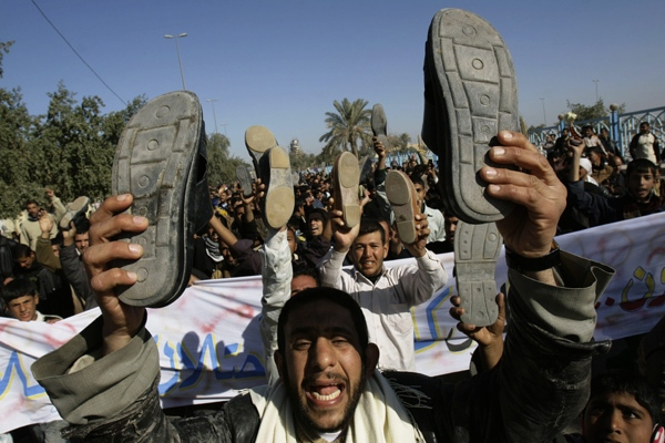 Iraqis raise their shoes as hundreds demanded a release for Iraqi journalist Muntadhar al-Zeidi who threw his shoes at US President George W. Bush in Kufa, Iraq, Friday. Dec. 19, 2008. (AP / Alaa al-Marjani)