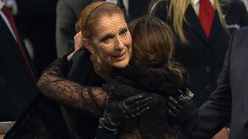 Celine Dion is hugged by a mourner at the visitation for Rene Angelil at Notre-Dame Basilica, in Montreal, Thursday, Jan. 21, 2016.
