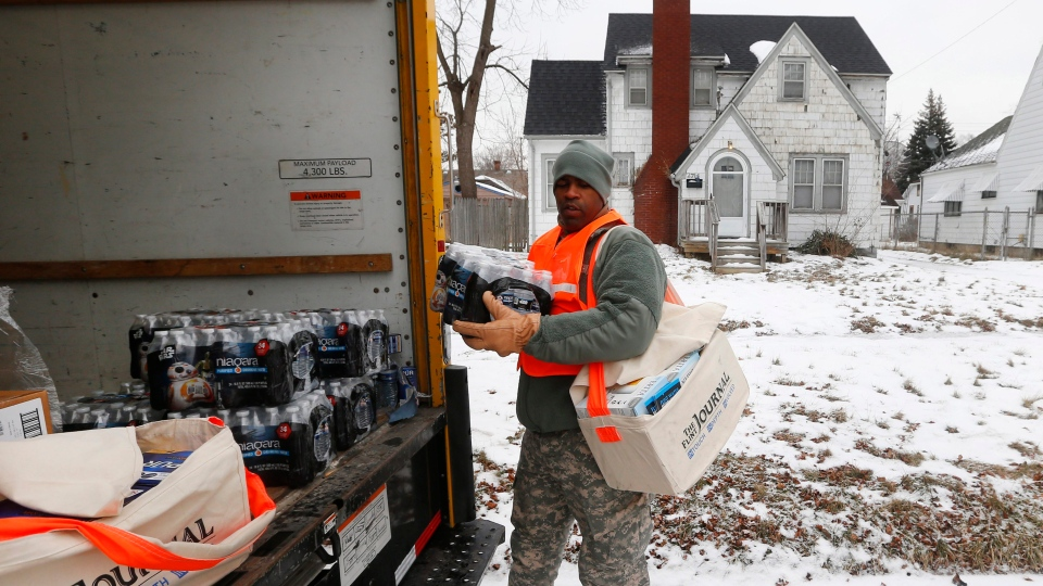 Michigan National Guard Specialist Lonnie Walker unloads bottled water and filters to distribute to residents, in Flint, Mich., on Thursday, Jan. 21, 2016. (AP Photo/Paul Sancya)