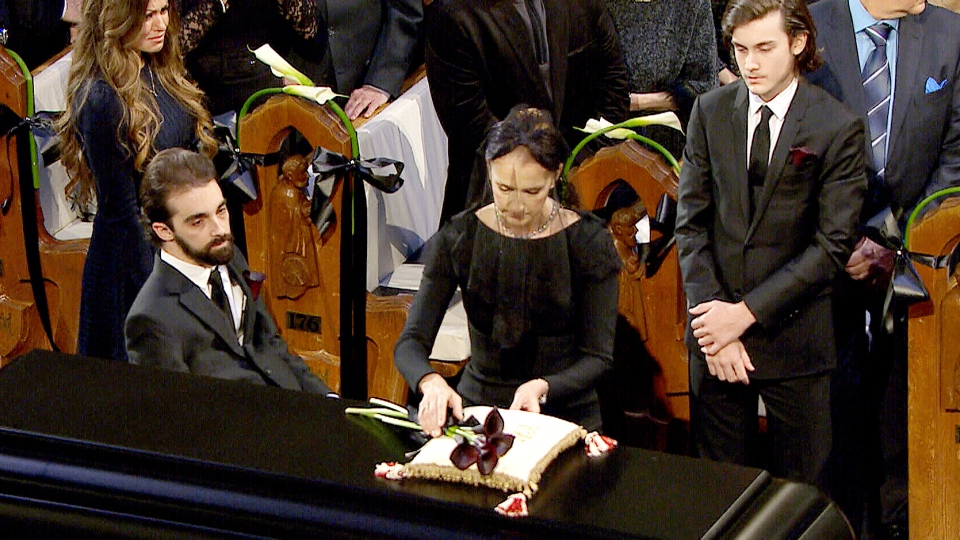 Celine Dion places flowers on the casket of her late husband Rene Angelil at his national funeral at Notre-Dame Basilica in Montreal, Friday, Jan. 22, 2016.