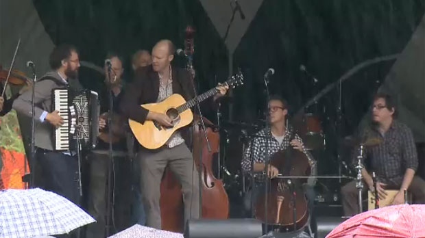 A side stage performance in the rain at the Calgary Folk Music Festival