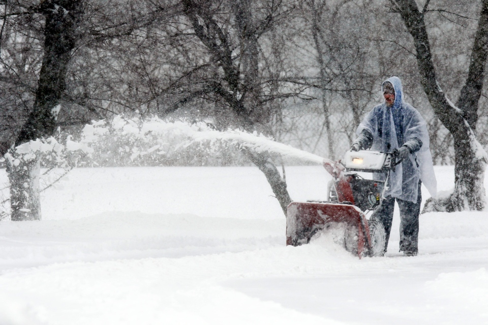 Maintenance worker Brandon McCullah clears a parking lot with a snowblower Friday, Jan. 22, 2016, in Lexington, Ky. (AP/James Crisp)
