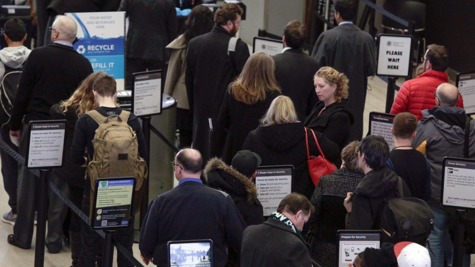 Travelers wait in a security line at O'Hare International Airport Friday, Jan. 22, 2016 in Chicago. Airlines at Chicago's two major airports have canceled 215 flights largely due to a blizzard threatening down on the East Coast. (AP / Teresa Crawford)