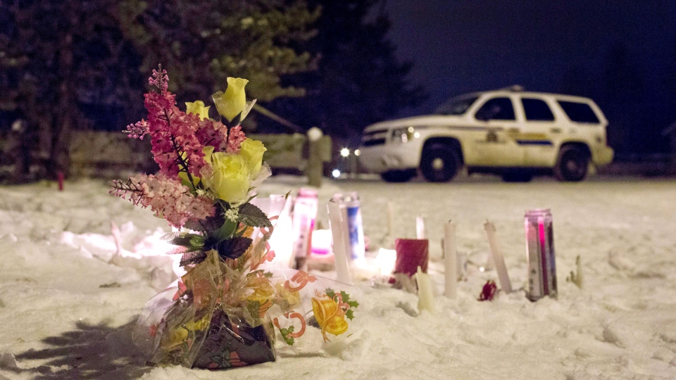 Candles and flowers placed as a memorial lay near the La Loche, Sask., junior and senior high school on Saturday, January 23, 2016. A shooting Friday left four people dead. (Jason Franson / THE CANADIAN PRESS)
