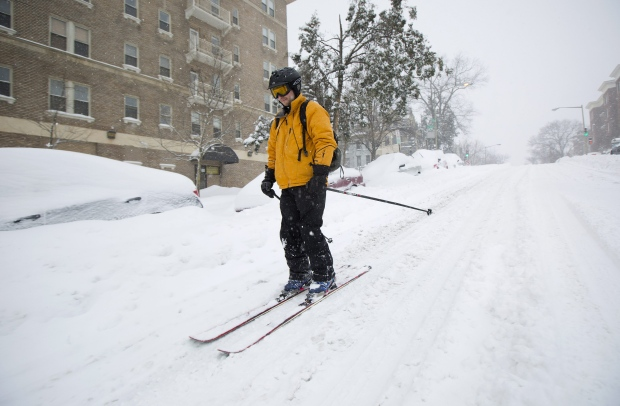 Man skiis down street during U.S. snowstorm