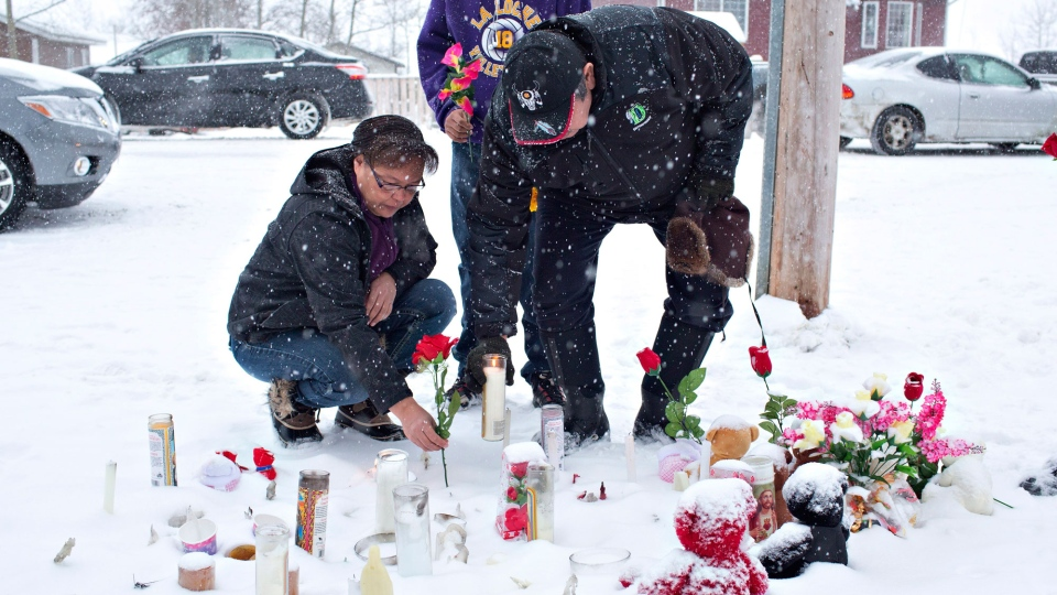 A family La Loche, Sask., pay their respects on Saturday, Jan. 23, 2016 to the victims of a Friday school shooting. The shooting left four people dead. (Jason Franson/THE CANADIAN PRESS)