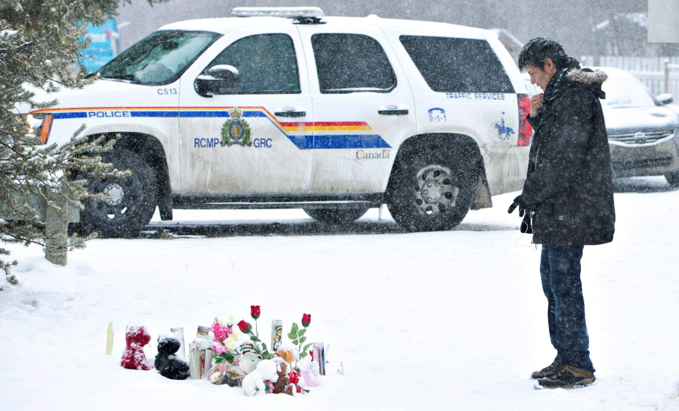 A resident of La Loche, Sask., pays his respects on Saturday, Jan. 23, 2016 to the victims of a Friday shooting. The shooting left four people dead. THE CANADIAN PRESS/Jason Franson