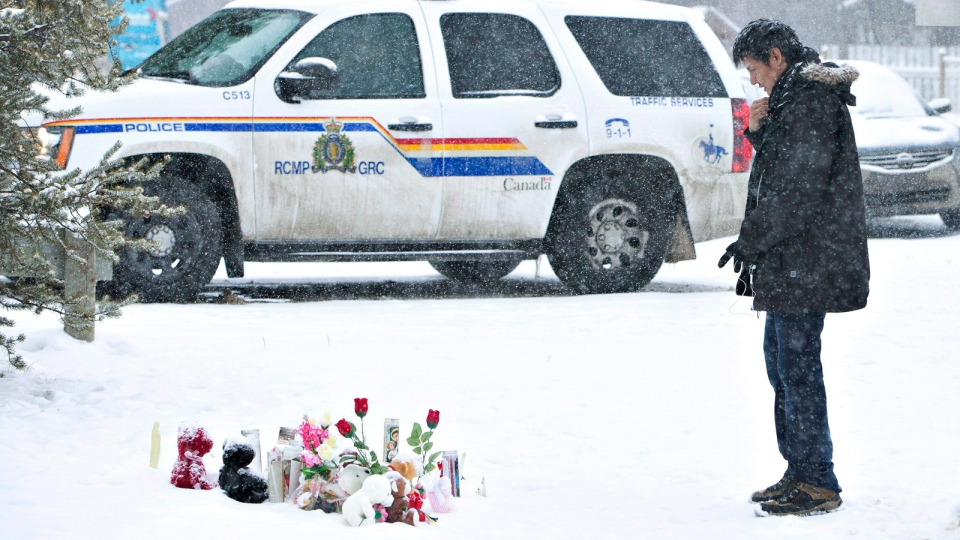 A resident of La Loche, Sask., pays his respects on Saturday, January 23, 2016 to the victims of a Friday school shooting. The shooting left four people dead. (Jason Franson /THE CANADIAN PRESS)