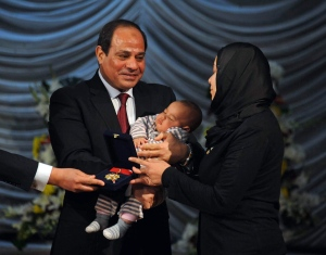 In this photo provided by Egypt's state news agency, MENA, Egyptian President Abdel-Fattah el-Sissi holds a child as he presents a medal to the widow of a policeman killed in militant attacks, at a ceremony marking Police Day, which falls on Jan. 25, the anniversary of the 2011 uprising that toppled longtime ruler Hosni Mubarak, in Cairo, Egypt on Jan. 23, 2016. (Fady Fares, MENA via AP)
