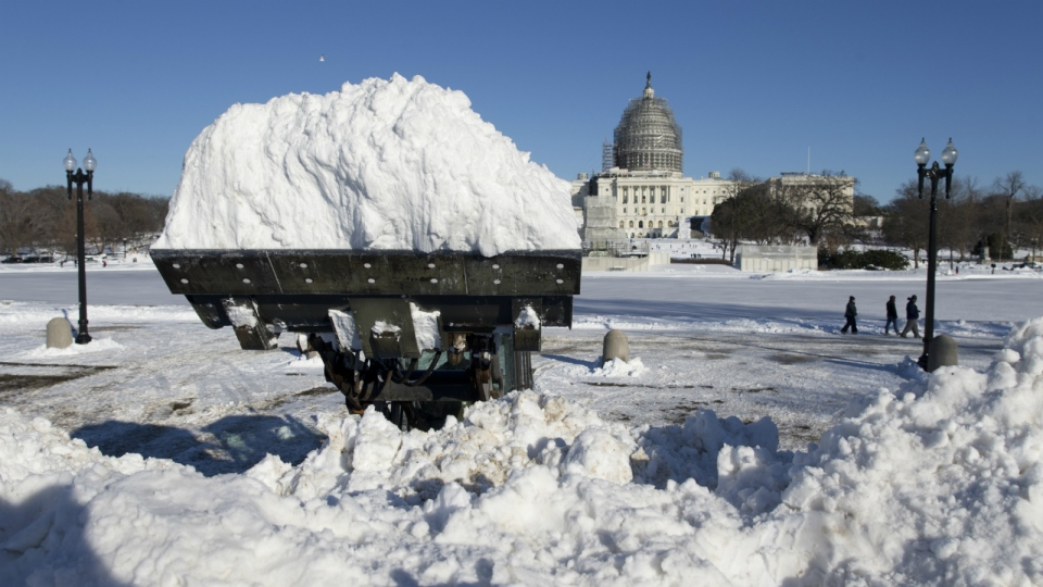A loader piles a full bucket of snow in front of the U.S. Capitol Building in Washington on Sunday, Jan. 24, 2016. (AP / Carolyn Kaster)