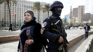 A woman walks past an Egyptian policeman, a day ahead of the fifth anniversary of the Jan. 25, 2011 uprising in Tahrir Square, Cairo, Egypt on Sunday, Jan. 24, 2016. (AP / Roger Anis)