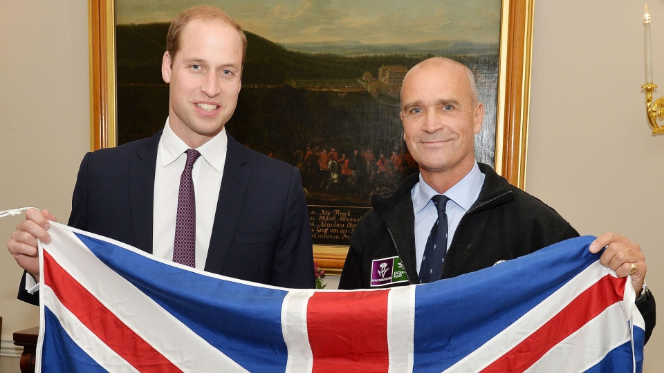 Former Army officer Henry Worsley, right, is seen with Prince William as they hold the British flag in London on Oct. 19, 2015. (John Stillwell/PA via AP)