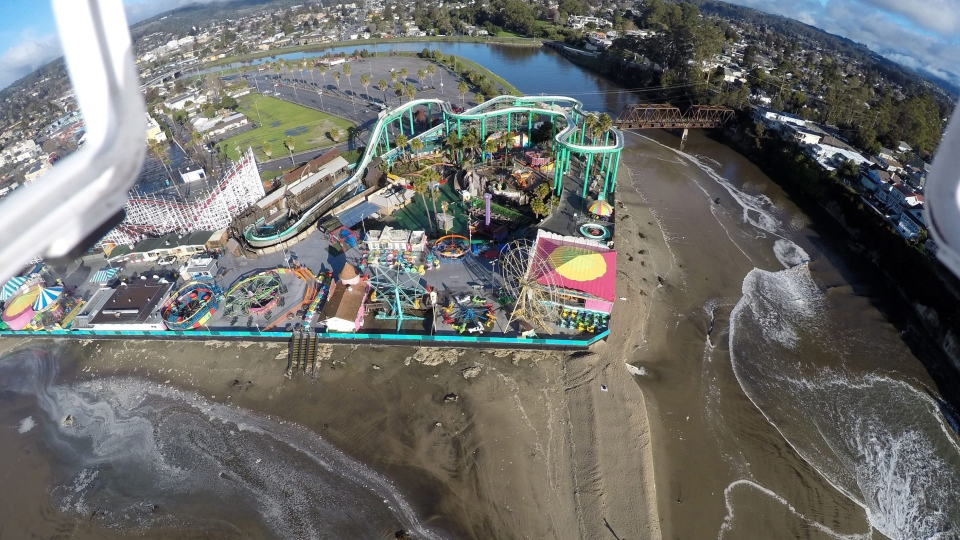 This Jan. 7, 2016 photo provided by The Nature Conservancy shows the San Lorenzo River overflowing around the Santa Cruz Beach Boardwalk, an oceanfront amusement park in Santa Cruz, Caif. (Matt Merrifield via AP)