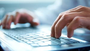 An employee types on a computer keyboard (Pressmaster/shutterstock.com)