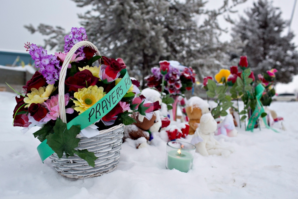 A memorial grows as more people leave flowers and candles in front of the La Loche Community School in La Loche, Sask. on Sunday, January 24, 2016. Four people were killed Friday in shootings at a local school and a home in the small town. THE CANADIAN PRESS/Jason Franson