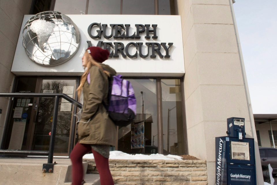A woman walks by the Guelph Mercury office in Guelph, Ont. on Monday, Jan. 25, 2016. (The Canadian Press/Hannah Yoon)