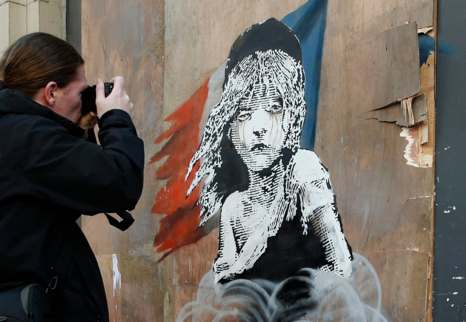 A man takes a photo of a new artwork by British artist Banksy opposite the French Embassy, in London, Monday, Jan. 25, 2016. The artwork depicts the young girl from the musical Les Miserables with tears streaming from her eyes as a can of CS gas lies beneath her. The work is criticizing the use of teargas in the refugee camp in Calais. (AP Photo/Alastair Grant)