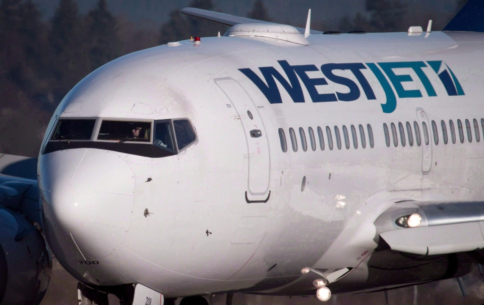 A pilot taxis a Westjet Boeing 737-700 plane to a gate after arriving at Vancouver International Airport in Richmond, B.C., on February 3, 2014. (Darryl Dyck / THE CANADIAN PRESS)
