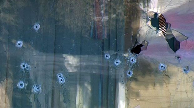 Bullet holes riddle the front window of a Huntington Hills home after an officer-involved shooting on Sunday.