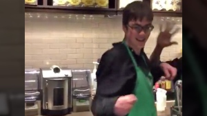 Sam is seen dancing at a Toronto Starbucks with his manager Chris in the background.